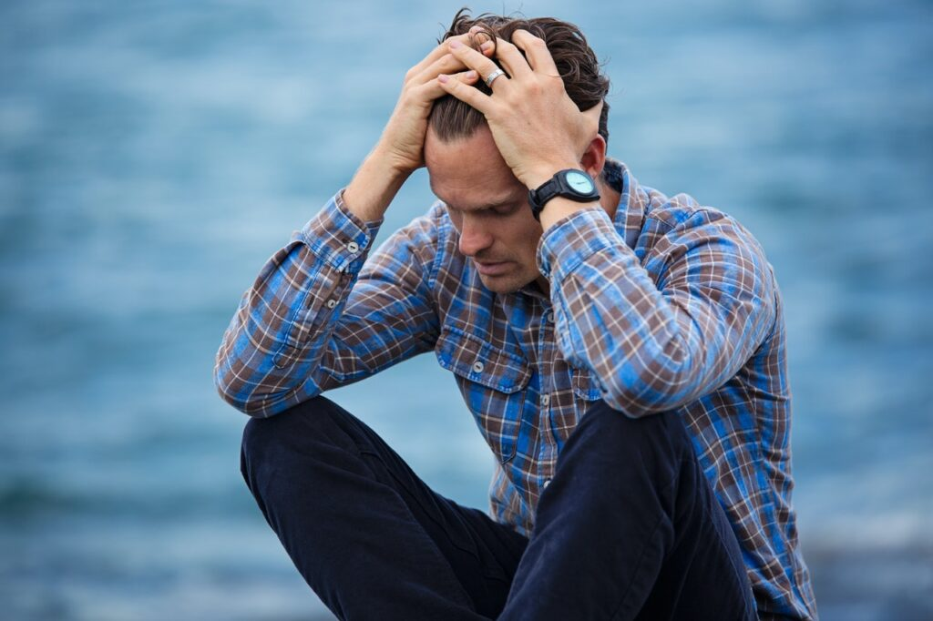 a stressed man beside the ocean